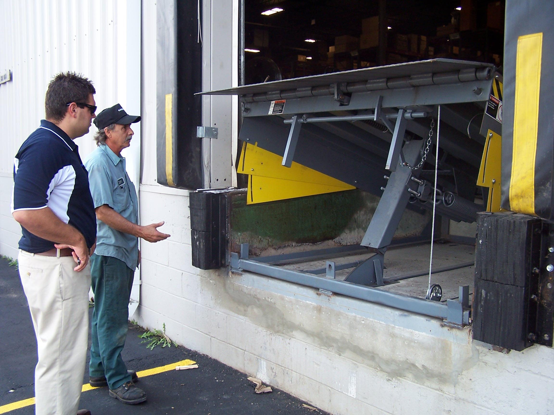 McKee service techs inspecting a loading dock leveler for an overhead door garage bay