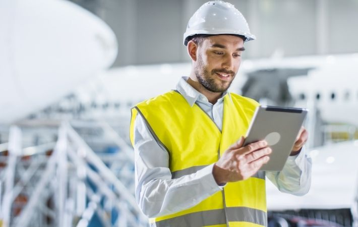 McKee service tech in high-vis vest and hardhatdoing walkthrough inspection with iPad